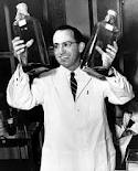 Salk holding up jars of cells used to grow the virus for his vaccine